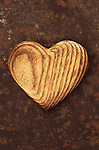 Close up from above of wooden heart shape carved to show tree rings and woodgrain lying on rusty metal sheet