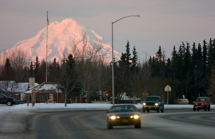 Alpenglow lights the face of Mount Redoubt at sunrise as traffic moves on the Kenai Spur Highway through downtown Kenai, Alaska. The 10,197-foot active volcano is the dominant landmark on the city's horizon.