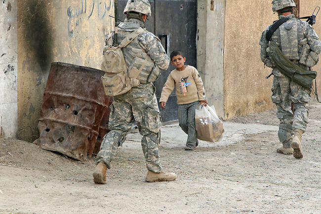 Pfc. Jesse Ball, 20, of Houston, Texas, and Pfc. Joseph McKenzie, 21, of Chicago, Ill., walk past a boy while on patrol in Samarra, Iraq. Soldiers with Company C, 2nd Battalion, 327th Infantry Regiment say they encounter hostile fire and IEDs almost daily in the city, but these photos were taken during a rare four-day period when no attacks occurred. Nov. 16, 2007. DREW BROWN/STARS AND STRIPES