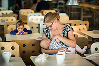 A mother breastfeeds her baby at the table of an in-store restaurant.  An older child is drinking from a bottle in the background,