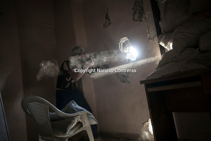 A rebel fighter fires over his enemy's position as skirmishes spark out at the front line in Bustan Al Qasr frontline in Aleppo, Syria.