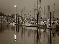 Moon set over Newport Harbor with fishing boats. Newport, Oregon