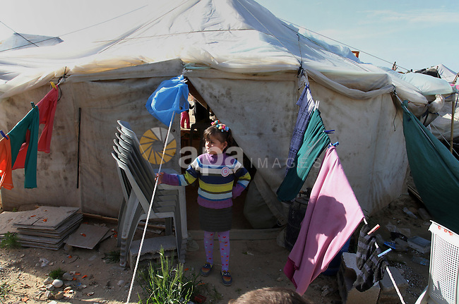 A Palestinian girl plays outside her a tent donated by a charity organisation as temporary housing for those whose houses were destroyed during a seven-week Israeli offensive, in Khuzaa, east of Khan Younis, in the southern Gaza Strip, on March 01, 2015. Photo by Abed Rahim Khatib