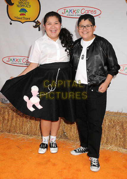 Raini Rodriguez, Rico Rodriguez.20th Annual Camp Ronald McDonald Halloween Carnival held at the Universal Studios Backlot, Universal City, California, USA..October 21st, 2012.full length black white skirt shirt jacket top glasses trousers siblings brother sister family poodle print .CAP/ADM/BP.©Byron Purvis/AdMedia/Capital Pictures.