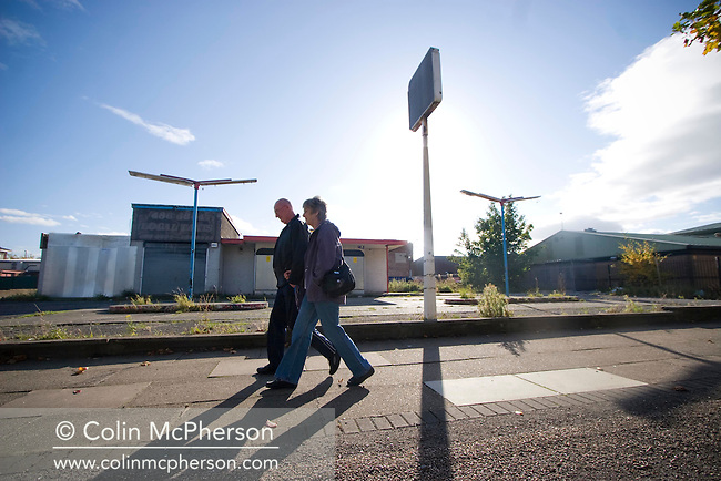 A couple walking past a derelict shop and petrol station in the Liverpool suburb of Speke. The area has been defined as one of Britain's most deprived and is seen as vulnerable to cuts in investment should the UK enter a full recession as a result of the credit crunch.