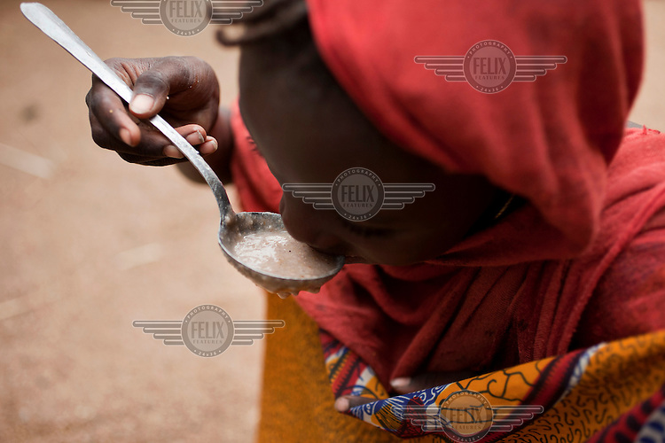 A child eats a spoon of porridge in the village of Luga. Across the Sahel drought, exacerbated by a rise in global food prices, has left about 40% of Niger's population facing severe food insecurity. This particularly affects women and children with an estimated 127,000 children under five years old predicted to suffer from severe malnutrition during 2012.