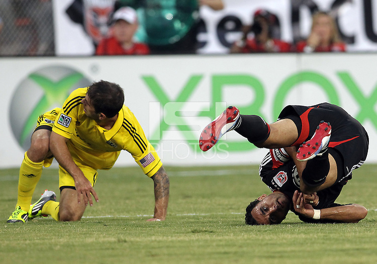 WASHINGTON, DC - AUGUST 4, 2012:  Dwayne DeRosario (7) of DC United falls after being hit by Carlos Mendes (4) of the Columbus Crew during an MLS match at RFK Stadium in Washington DC on August 4. United won 1-0.