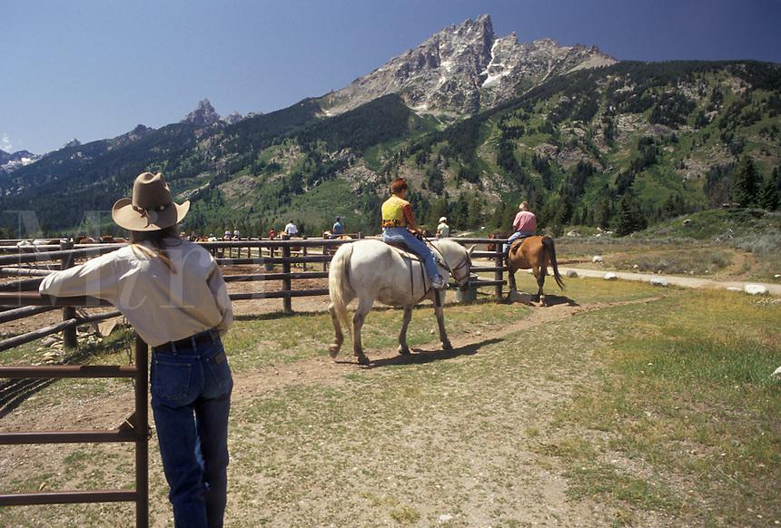 "AJ3580, horseback riding, trail ride, Grand Teton National Park, Wyoming, Grand Teton, Rocky Mountains, Grand Teton Mountains, Teton Range, A group of people riding horses leave the corral at Colter Bay Village for the """"Teton Trail Ride"""" through the Grand Teton National Park in the state of Wyoming. A view of the Teton mountain range is in the distance."