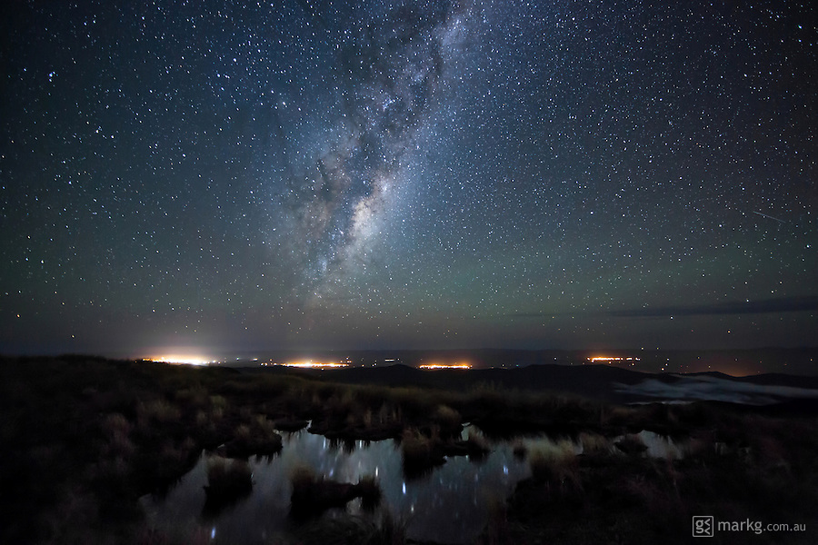 The Milky Way rises over the Wairarapa on the North Island of New Zealand. The lights from the towns of Masterton, Carterton, Greytown, Martinborough and Featherston can be seen in the image from left to right. The photo was shot from on top of the Tararua Ranges at a height of around 1300m above sea level, and with the area being so remote and a long walk from anywhere, I had to be flown in by helicopter operated by Kapiti Heliworx for the shoot.