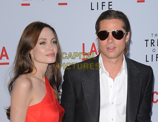 "ANGELINA JOLIE & BRAD PITT.L.A. Premiere of ""The Tree of Life"" held at The Bing Theatre at LACMA in Los Angeles, California, USA. .May 24th, 2011    .half length dress black suit white shirt sunglasses shades one shoulder red orange red headshot portrait.CAP/RKE/DVS.©DVS/RockinExposures/Capital Pictures."