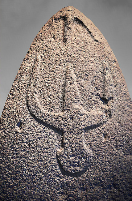 Late European Neolithic prehistoric Menhir standing stone with carvings on its face side. The representation of a stylalised male figure starts at the top with a long nose from which 2 eyebrows arch around the top of the stone. below this is a carving of a falling figure with head at the bottom and 2 curved arms encircling a body above. Excavated from Genna Arrele II. Menhir Museum, Museo della Statuaria Prehistorica in Sardegna, Museum of Prehoistoric Sardinian Statues, Palazzo Aymerich, Laconi, Sardinia, Italy