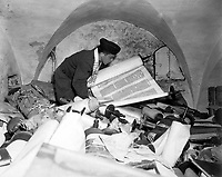 "In the cellar of the Race Institue in Frankfrut, Germany, Chaplain Samuel Blinder examines one of hundreds of ""Saphor Torahs"" (Sacred Scrolls), among the books stolen from every occupied country in Europe.  July 6, 1945.  T3c. Irving Katz. (Army)<br /> NARA FILE #:  111-SC-209154<br /> WAR & CONFLICT BOOK #:  1100"