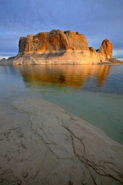 The final rays of the day illuminate Castle Butte on Lake Powell in the Glen Canyon National Recreation Area on the Arizona-Utah border, USA