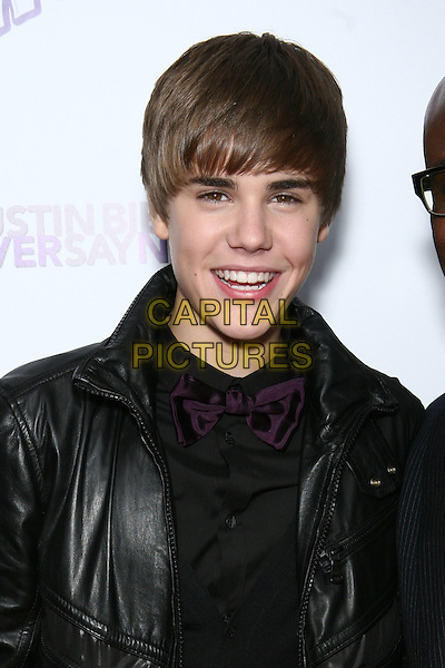 "JUSTIN BIEBER.Special Screening of ""Justin Bieber: Never Say Never"" at the Regal 42nd Street E-Walk Cinemas, New York, USA, 2nd February 2011..portrait headshot black leather purple bow tie shirt jacket smiling .CAP/LNC/TOM.©LNC/Capital Pictures."