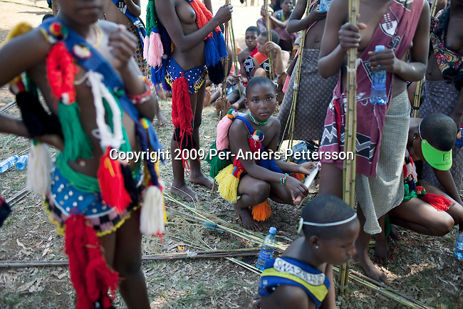 LUDZIDZINI, SWAZILAND - AUGUST 30: Young girls wait to dance at a traditional Reed dance ceremony at the Royal Palace on August 30, 2009, in Ludzidzini, Swaziland. About 80.000 virgins from all over the country attended this yearly event, the biggest in Swazi culture. It was founded to celebrate the beauty of Swazi women and girls. King Mswati III, and absolute monarch, was born in 1968 and he has 14 wives and many children. The king danced with his men in front of the 80.000 girls. Many of the girls hope to get noticed by the king and to be chosen as a future wife, a ticket from poverty and into a life of privilege and luxury. The country is one of the poorest in the world and it is struggling with a high prevalence of HIV-Aids and severe poverty. (Photo by: Per-Anders Pettersson).....