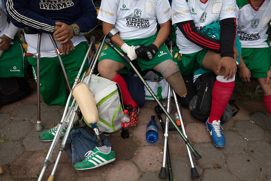 """Players from Guerreros Aztecas remove their prosthetic legs and get changed before a match against Los Dragones (""""the Dragons"""")  in Deportivo Tlalli II in Talnepantla, Mexico on September 27, 2014. Guerreros Aztecas (""""Aztec Warriors"""") is Mexico City's first amputee football team. Founded in July 2013 by five volunteers, they now have 23 players, seven of them have made the national team's shortlist to represent Mexico at this year's Amputee Soccer World Cup in Sinaloathis December.The team trains twice a week for weekend games with other teams. No prostheses are used, so field players missing a lower extremity can only play using crutches. Those missing an upper extremity play as goalkeepers. The teams play six per side with unlimited substitutions. Each half lasts 25 minutes. The causes of the amputations range from accidents to medical interventions – none of which have stopped the Guerreros Aztecas from continuing to play. The players' age, backgrounds and professions cover the full sweep of Mexican society, and they are united by the will to keep their heads held high in a country where discrimination against the disabled remains widespread.(Photo byBénédicte Desrus)"""