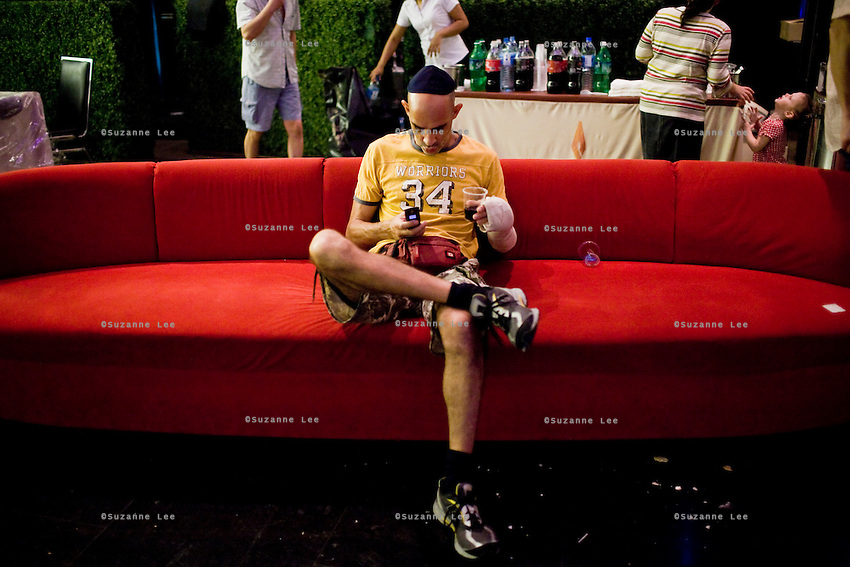 Shuki Rosenzweig sits on a couch at the Chanuka celebrations organised by Chabad Bangkok on 13th December 2009, at Paragon Mall's IMAX theater, Bangkok, Thailand. Shuki broke his left hand in a competition last week...Shuki, aged 40, is a professional Muay Thai Boxing fighter (champion) and trainer who has lived for 9 years in Thailand. He is famous in Israel as the authority of this sport. Started at the age of 12 in boxing in Israel, Jerusalem. Used to work in the fish market. His father is a 'legend' in Jerusalem fish market. Shuki stopped working with his dad about 13 years ago. He has opened some muay thai gyms in Thailand in the past. He currently has about 5 Israeli fighters under his training in Bangkok, besides fighters of other nationalities. Shuki found religion in Bangkok with Chabad about 4 years ago. He never misses Shabbat and loves to sing the songs of prayer, priding himself with a good voice..Photo by Suzanne Lee / For Chabad Lubavitch