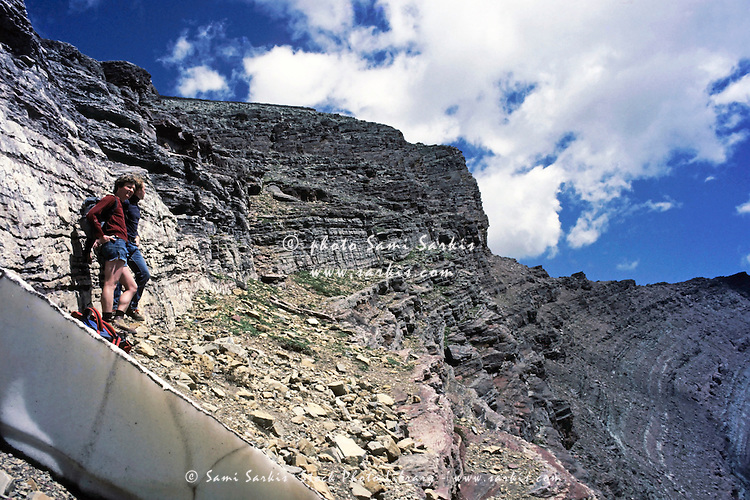 Two climbers standing on the rock face of Mount Henkel looking at view, Glacier National Park, Montana, USA.
