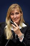 Vrouw aan het werk, overlegt zittend aan aan bureau met telefoon in haar hand, met haar collega over de voortgang van een project.