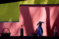 A Mexican man walks in front of a brightly painted wall.