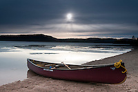 A canoe on a beach at dusk on a frozen Smoothwater Lake during an early spring trip to Lady Evelyn-Smoothwater Provincial Park in Ontario Canada.