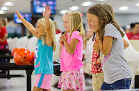 NWA Democrat-Gazette/JASON IVESTER <br /> Maddy Kirby (from left), 6, Penelope Long, 6, Isabella Collins, 7, cheer a friend on Thursday, Aug. 6, 2015, at the Rogers Bowling Center. The girls were on a field trip with others from the Bentonville School District Adventure Club. Students on traditional calendars return to class on Aug. 18.