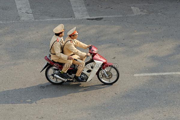 Asia, Vietnam, Hanoi. Hanoi old quarter. Two vietnamese officials riding on a motorbike through Hanoi.