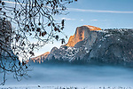 Winter fog fills the meadow as the sun lights up Half Dome.