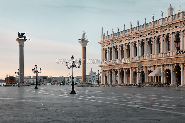 The Biblioteca Nazionale Marciana, or National Library of St Mark's, built in Renaissance style in 1537-53 by Jacopo Sansovino, then extended by Vincenzo Scamozzi in 1588, on the Piazzetta San Marco, between the Piazza San Marco and the Venetian lagoon, Venice, Italy. The 2-storey building is lined with a Doric arcade on the ground floor and Ionic arcade on the first floor, with sculptural decoration and a line of rooftop statues. The library houses an important collection of classical, Oriental and medieval codices and manuscripts. To the left are the Columns of San Marco and San Todaro, with statues of the Byzantine saint San Teodoro Amasea and St Mark the evangelist in the form of a winged lion, 12th century, by Nicolo Barattieri. The historical centre of Venice is listed as a UNESCO World Heritage Site. Picture by Manuel Cohen