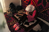 "New bride Dinara, 22, feels depressed and sits behind a curtain on the side of the couple's room during her week-long wedding party. ""I don't know if Afmat really loves me or not. Maybe he doesn't care about me even though he kidnapped me"" she says. Dinara was kidnapped by Ahmat who wanted to marry her. After resisting for 5 hours, she finally accepted. 'I didn't know Ahmad well and didn't want to stay there. But I accepted because this is our tradition' Dinara says. Although illegal, bride kidnapping is common in rural parts of Kyrgyzstan. Each year around 16, 000 women become married after being kidnapped. They are known as 'Ala Kachuu' that translates as 'to grab and run away'. Defenders of the continuation of the practice sight tradition. However, during Soviet Times it was rare, and parents generally arranged marriages.."