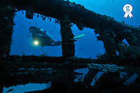 Woman diver with torch exploring shipwreck (Licence this image exclusively with Getty: http://www.gettyimages.com/detail/88015561 )