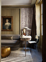 An 18th century portrait hangs in the library, whose walls are covered in oak panelling and a bark-inspired printed canvas and the room is furnished with a vintage Gio Ponti chair paired with a Jacques Adnet desk and C. Jere lamp