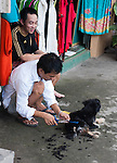 Hanoi, Vietnam, A man gives his dog a haircut as his frind sits by watching.photo taken July 2008.