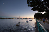 MASSACHUSETTS, Boston, Woman running on the waterfront with Boston Skyline at Dusk from Cambridge side of the Charles river