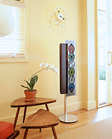 In a corner of the living room an upright music system stands next to a pair of retro side tables