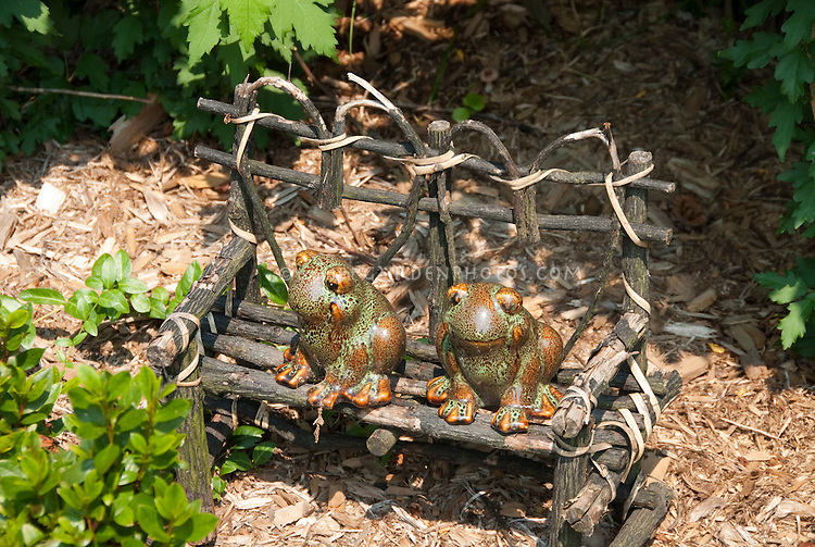 Garden ornaments: Curte ceramic frogs sitting on a miniature bench