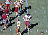 Washington Redskins running back John Riggins (44) looks for his helmet, which is on the ground, during a break in the action against the Houston Oilers at RFK Stadium in Washington, D.C. on September 15, 1985.  The Redskins won the game 16 - 13..Credit: Howard L. Sachs / CNP