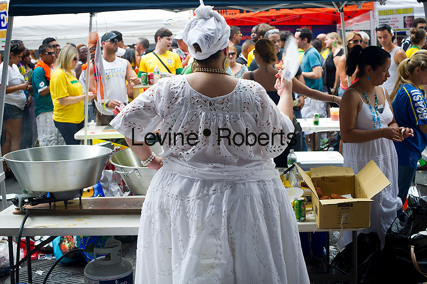A food vendor fans herself at the 28th Annual Brazil Day Festival in New York on Sunday, September 2, 2012.  The festival, which features food, music and other aspects of Brazilian culture, centers around West 46th Street in Midtown Manhattan, known as Little Brazil. (© Frances M. Roberts)