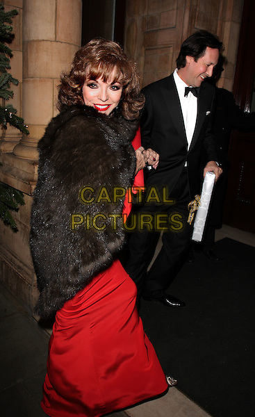 JOAN COLLINS & PERCY GIBSON.Christopher Biggins' 60th Birthday Party at the Landmark Hotel, Marylebone, London, England..December 15th, 2008.full length red dress black brown fur wrap clutch bag tuxedo profile married husband wife .CAP/ROS.©Steve Ross/Capital Pictures.