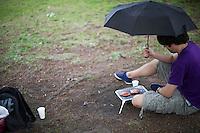Berlin, Ein Mann grillt am Donnerstag (09.05.13) im Mauerpark in Berlin mit einem mobilen Grill, und einem Regenschirm. Foto: Timur Emek/CommonLens