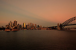 View of Circular Quays and the Opera House from Kirribilli by sunrise at the end of Summer.