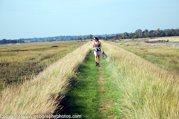 Woman walking flood defence bank, River Deben, Sutton, Suffolk