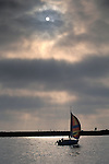 Sailboat sailing in harbor channel and sun and fog at sunset, Newport Beach, Orange County, California