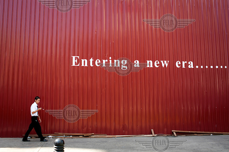 The words 'Entering a new era....' are painted on a temporary wall constructed around the Traders Hotel in central Rangoon (Yangon) which is undergoing renovations with a man walking by in the foreground. ...