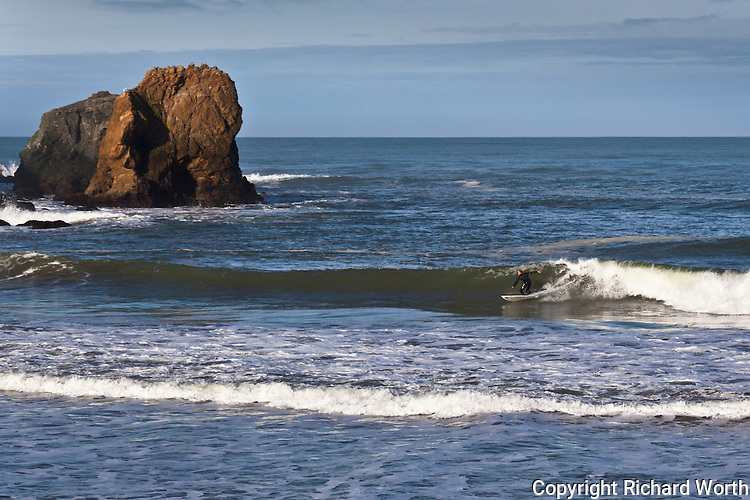 Nearby rocks glow with morning light while a surfer rides the waves in the cove at Rockaway Beach in Pacifica, California.