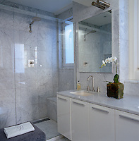 The bathroom walls are covered with soft grey Carrara marble tiles and furnished with Boffi lacquer cabinets