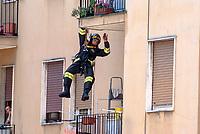 Milano. Un vigile del fuoco sospeso da una fune si cala da un balcone durante una emergenza --- Milan. A fireman suspended by a rope climbs down from a balcony
