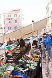 ITALY, Venice. Locals shopping at a floating produce market along a canal in the Castello district of Venice. Castello is the largest of the six sestieri of Venice.