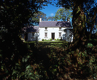 The exterior of a simple Welsh cottage with a slate roof glimpsed through a gap in the trees