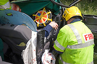 Firefighters and Paramedic crews working together treat an injured driver whose car had been involved in a Road Traffic Accident with a HGV UK. This image may only be used to portray the subject in a positive manner..©shoutpictures.com..john@shoutpictures.com